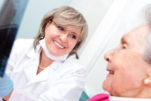 female dentist consults with female senior patient